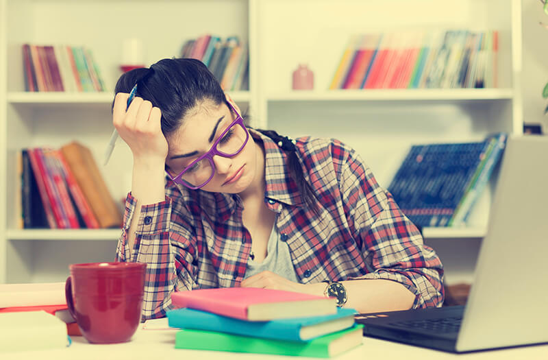 Female student with stack of homework