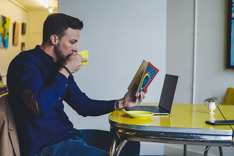 Man monitoring reading speed and drinking coffee