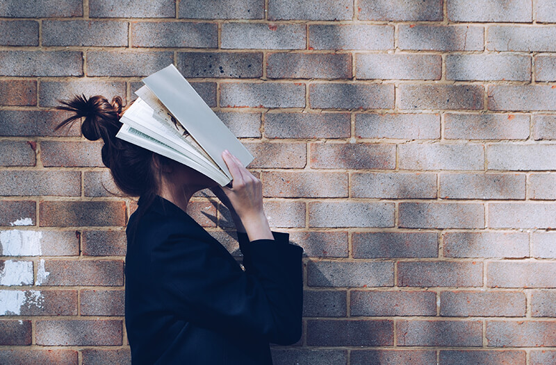 Female student holding an article over her head