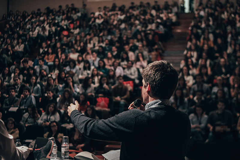 Young man giving a speech to a big audience