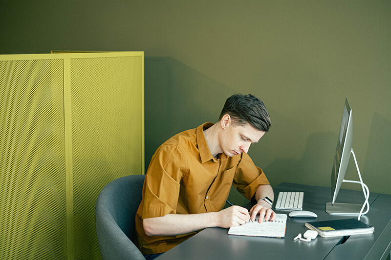 Young man taking notes near a computer to write an essay