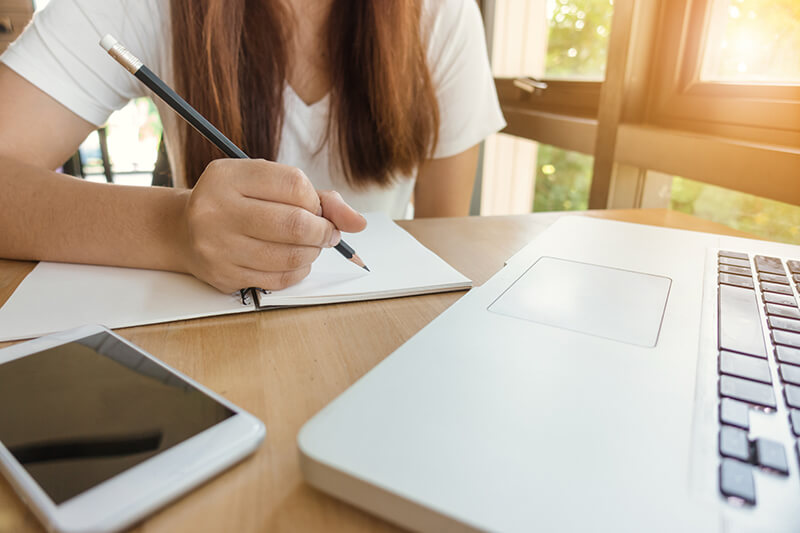 College student with her phone and laptop writing an analytical essay