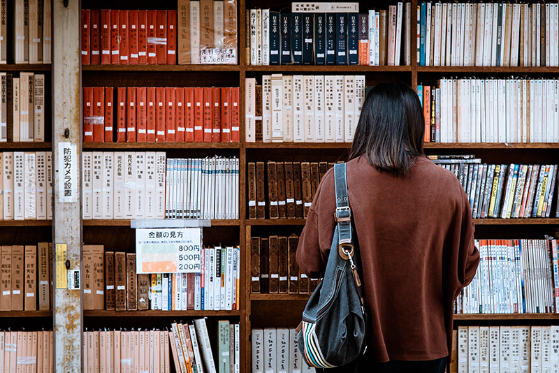 Asian student at the library looking for referencing materials