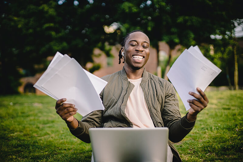 College student happily looking through research topics on his laptop