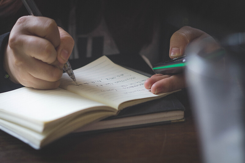 Closeup of student with a pen and smartphone writing a reflection paper