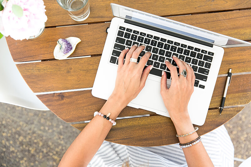 Female student hands typing an essay conclusion on a Macbook keyboard