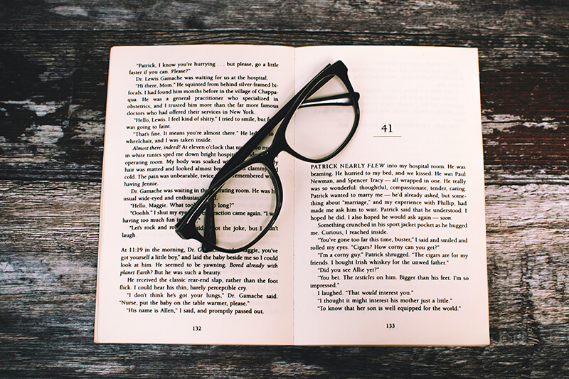 A set of eyeglasses placed on top of an open book of essays