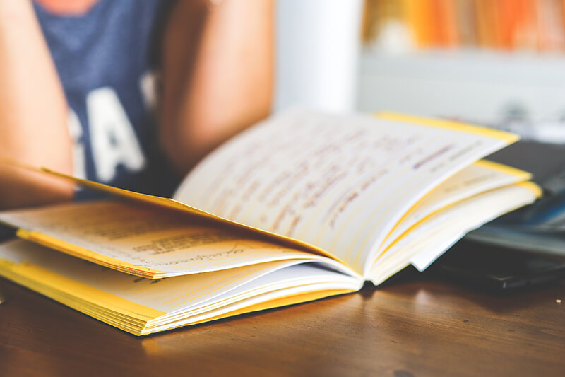 Close up of student flipping through information in a notebook