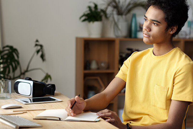Male student in a yellow shirt looking at a precis example for studying