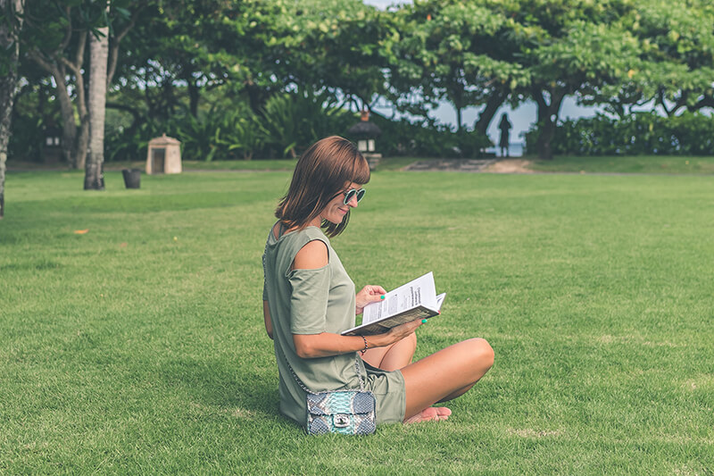 Female college student sitting outside reading a book in the sun