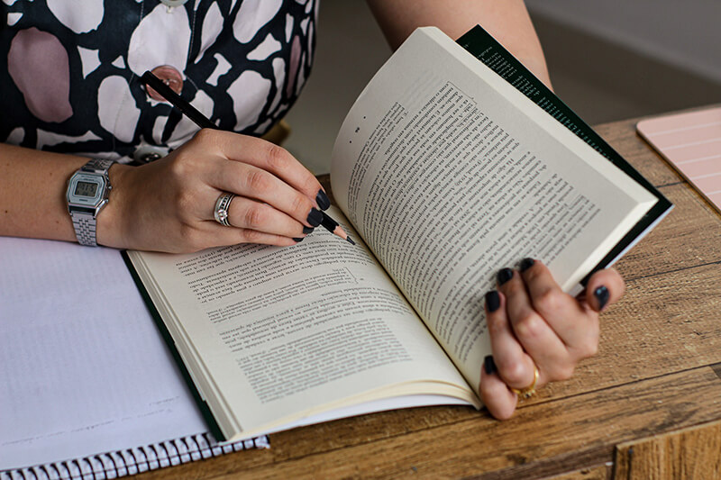 Closeup shot of a female student reading a book for her character analysis essay