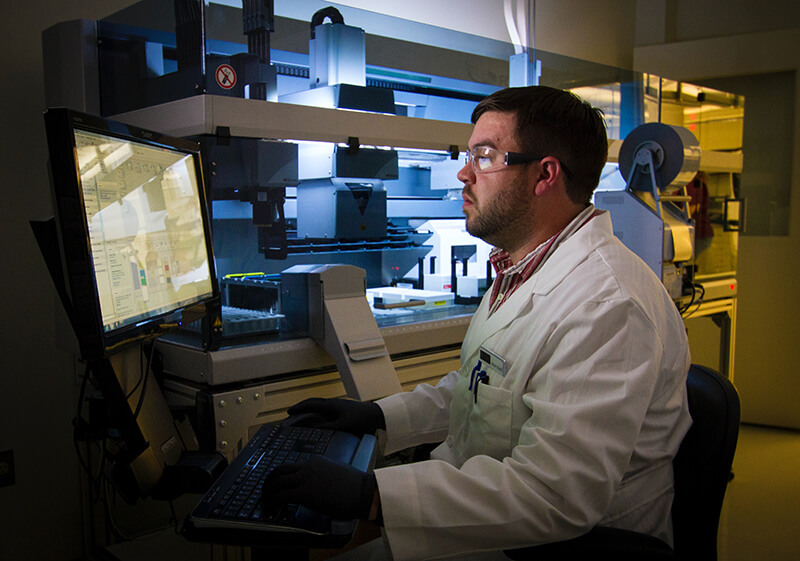 College science student writing a hypothesis for his experiment on the lab computer