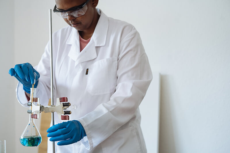 College science student performing a chemistry experiment in the lab