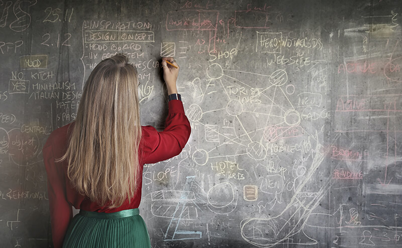 Female teacher writing a scientific equation using data on the blackboard