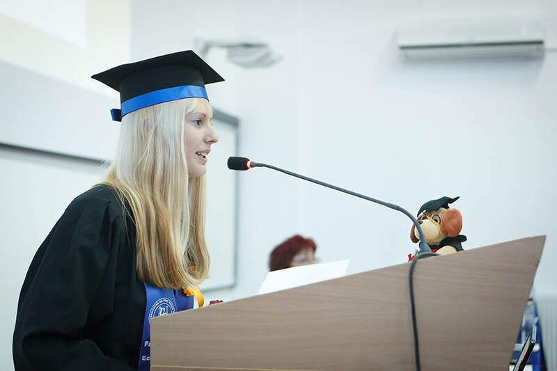 Young woman in graduation gown making a speech to an audience of graduates
