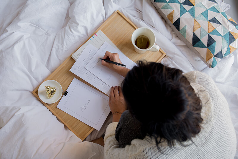 Female writing in a notebook while laying on her bed