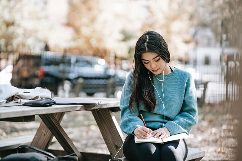 Female college student writing her essay on note paper with a pen