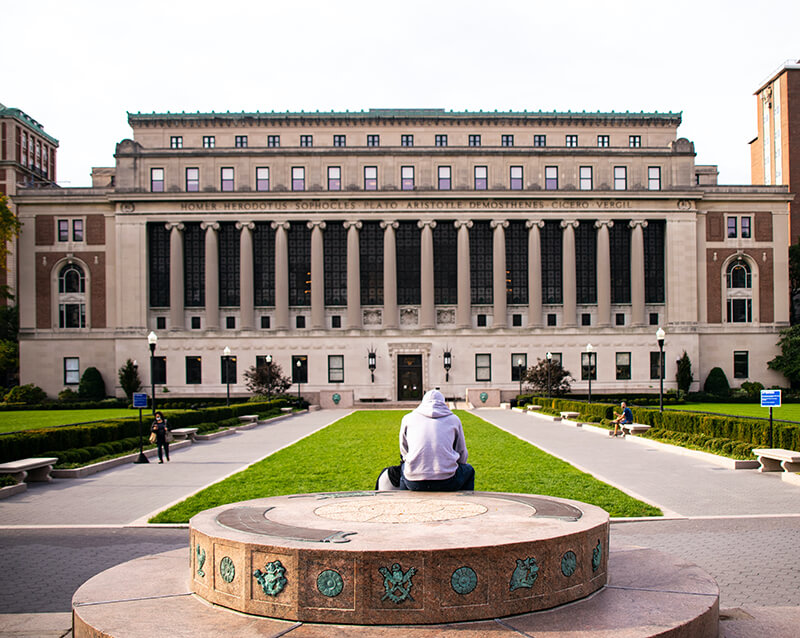 Student sitting on a bench in front of Columbia University in New York City, New York