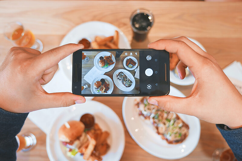 Influencer taking photos of the food on her plate to post on Instagram