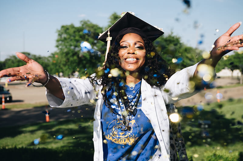 Female ivy league university graduate throwing confetti in the air