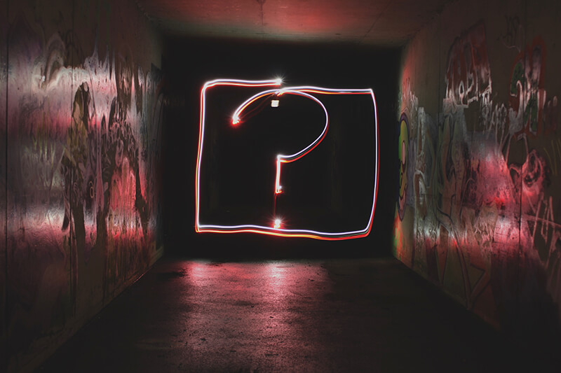 Neon sign in a hallway displaying a question mark