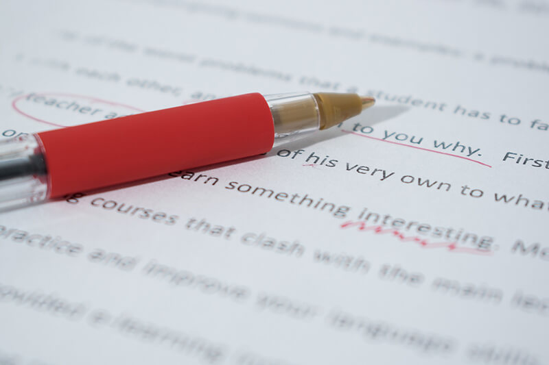 Closeup of red pen marking an essay with grammar mistakes