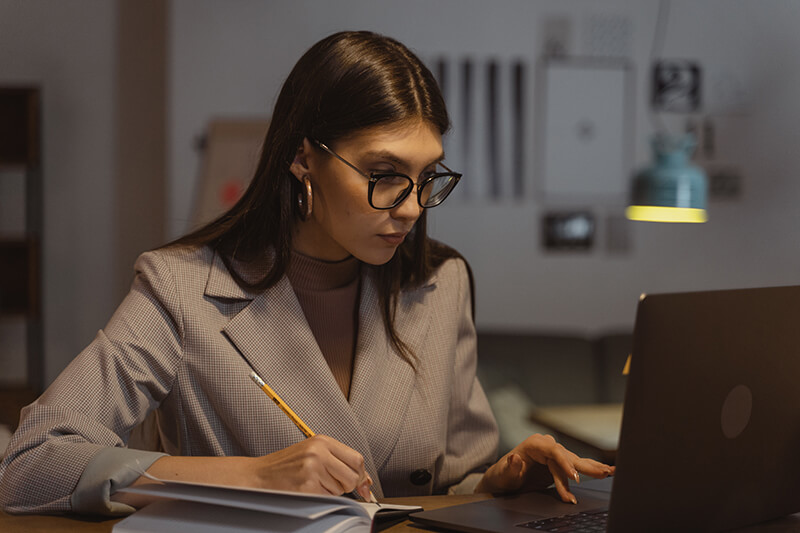 Female business woman using written notes to create a professional follow-up email