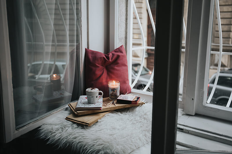 Tray with wellness candles and mood boosting supplies on a cozy corner of a bed