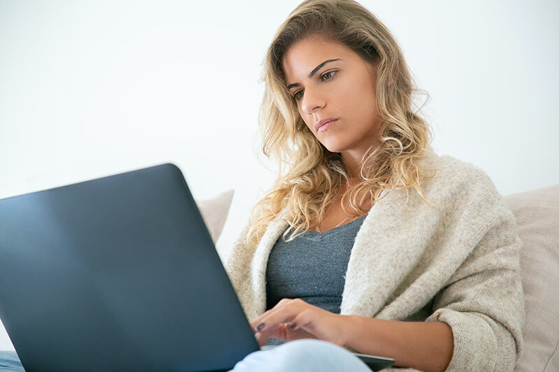 Young woman reading professional emails and job applications on a laptop