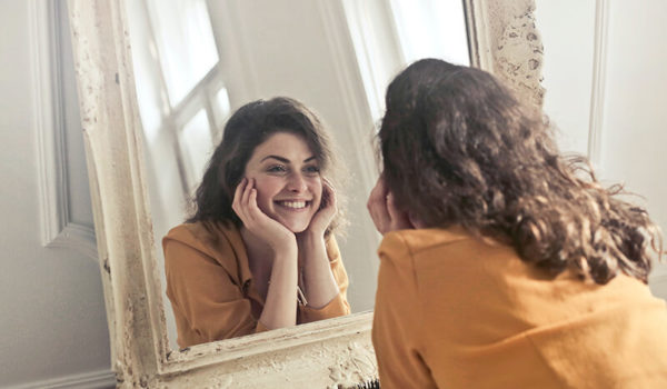 Young college student repeating positive affirmations in the mirror