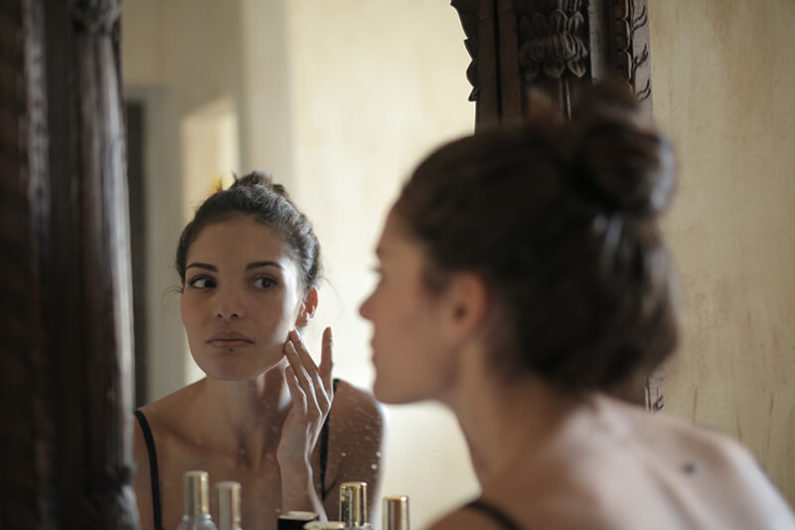 Young woman using some beauty self care ideas in the bathroom mirror