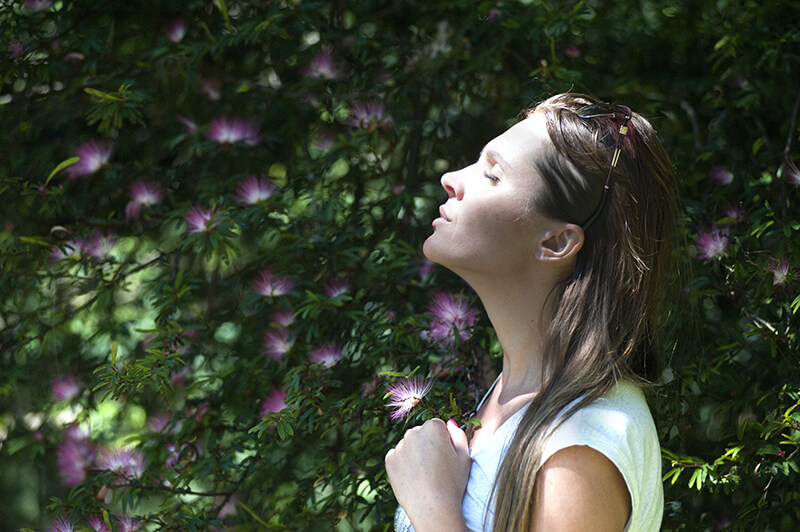 Young woman smelling flowers and embracing nature in her daily life