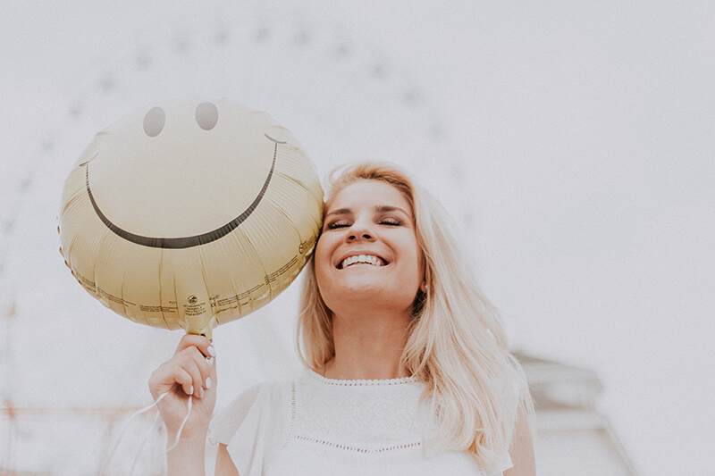 Young women embracing happiness with a smiling face balloon