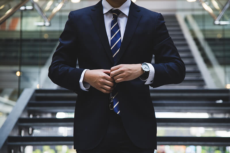 Male graduate wearing a suit walking into his job interview