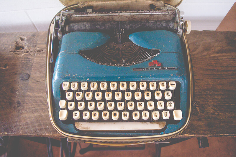Closeup of a blue typewriter sitting on a desk ready to write with classic literary techniques