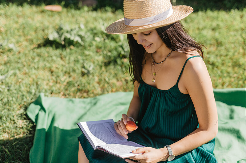 A woman sitting outside reading a book to flip through different literary techniques