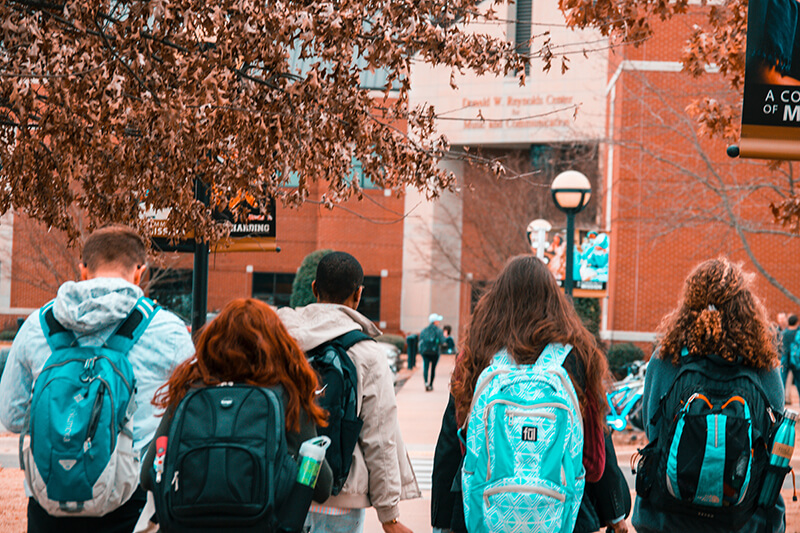 Group of students with backs turned walking into class together and making friendships