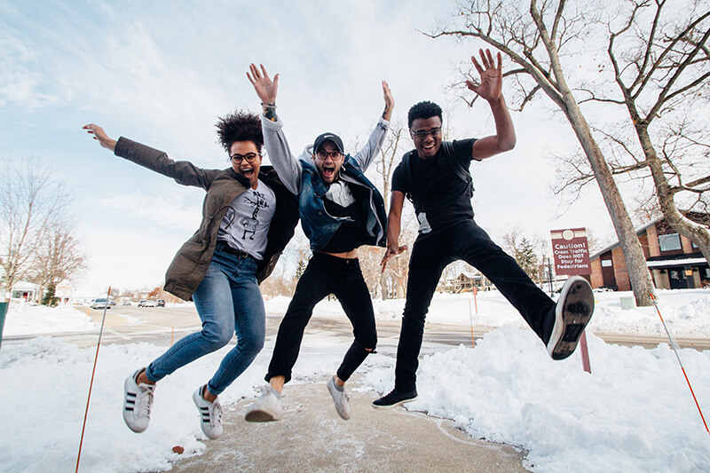 Three male friends jumping in the air and being happy outside together