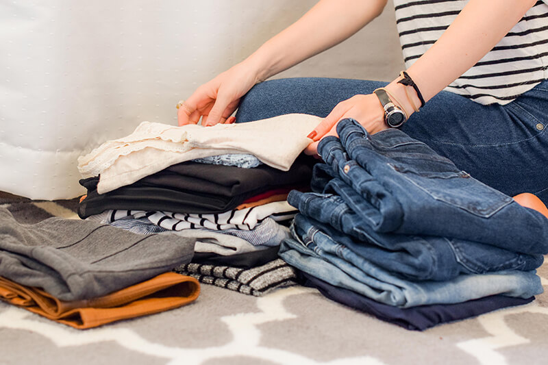 New student packing clothes to bring to their college dorm room