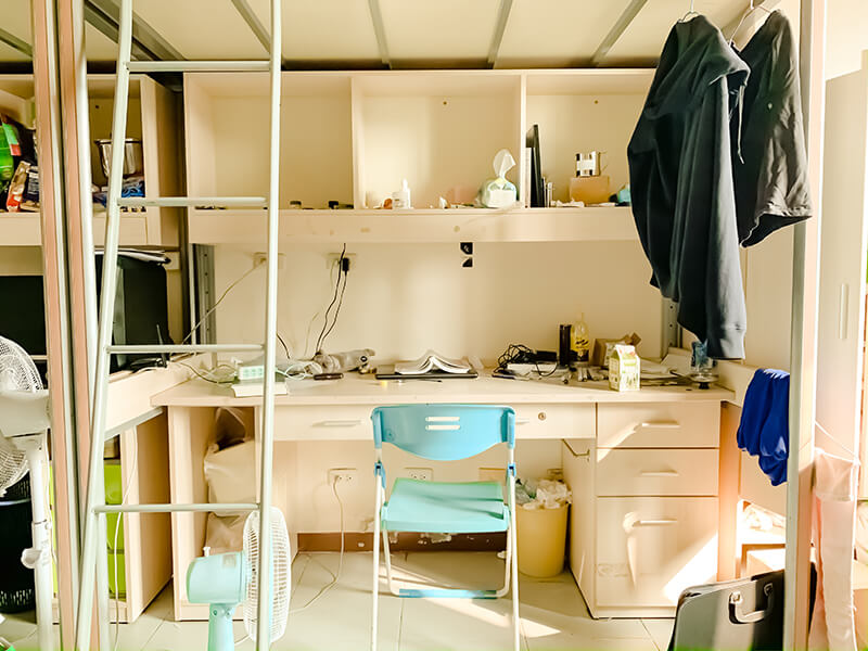 White college dorm room with bottom desk and bunk bed