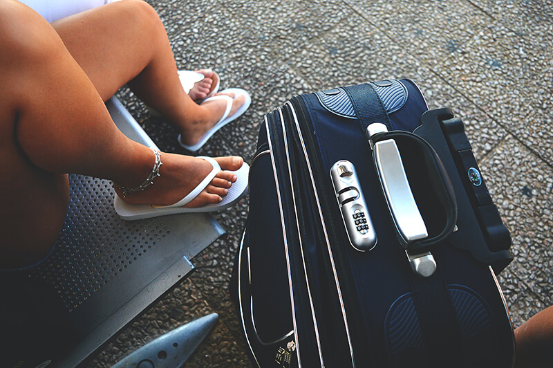 Freshman woman waiting to move in to her dorm with her suitcase by her feet