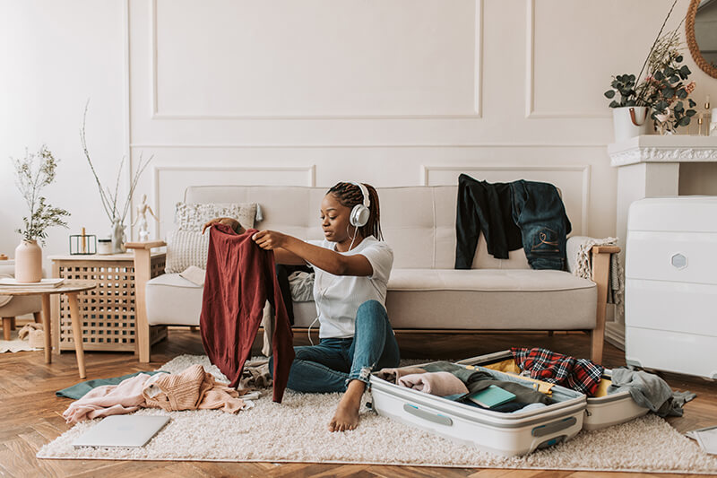 Female student packing for college while following a dorm room checklist