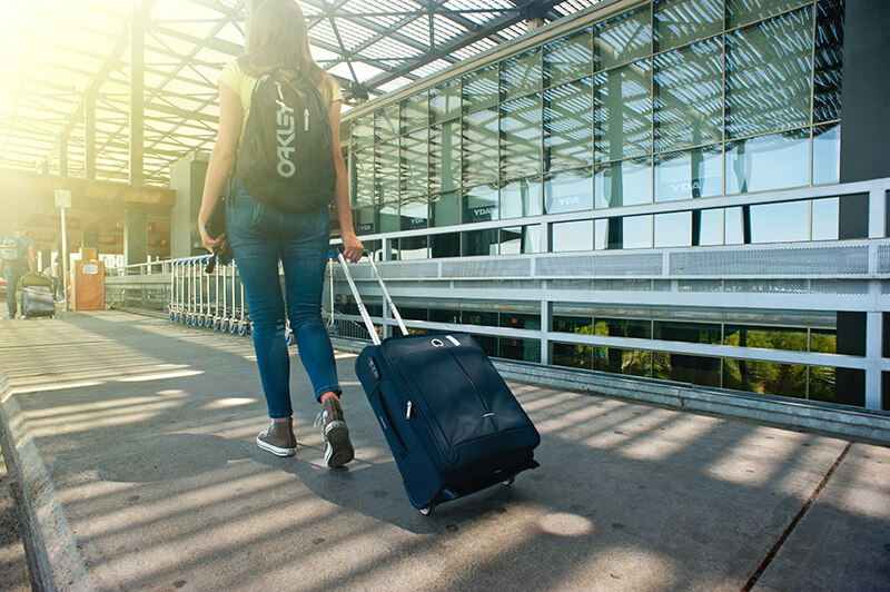 Female student rolling a suitcase on college move-in day