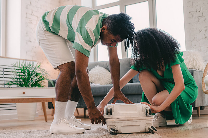 Man and woman helping each other pack for college following a college dorm checklist