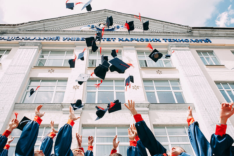 Greek alumni at graduation throwing their caps in the air to celebrate